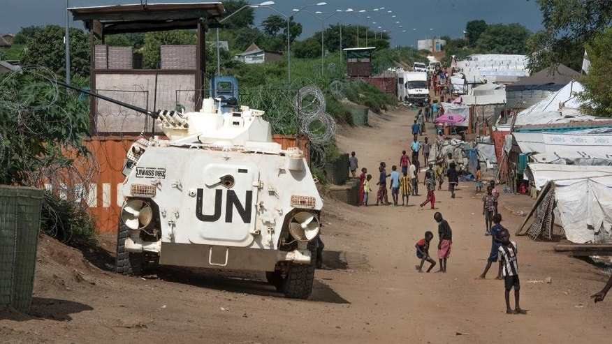 FILE - In this Monday, July . 25, 2016 file photo, some of the civilians sheltering in a United Nations base for fear of targeted killings by government forces walk by an armored vehicle and a watchtower manned by UN peacekeepers, in South Sudan's capital Juba. Part of President Donald Trump's proposed deep budget cuts in foreign aid could be significant reductions in U.N. peacekeeping missions in some of the world's most dangerous places. On Thursday, April. 6, 2017 the U.N. Security Council meets on the issue at the United States' request. (AP Photo/Jason Patinkin, File)