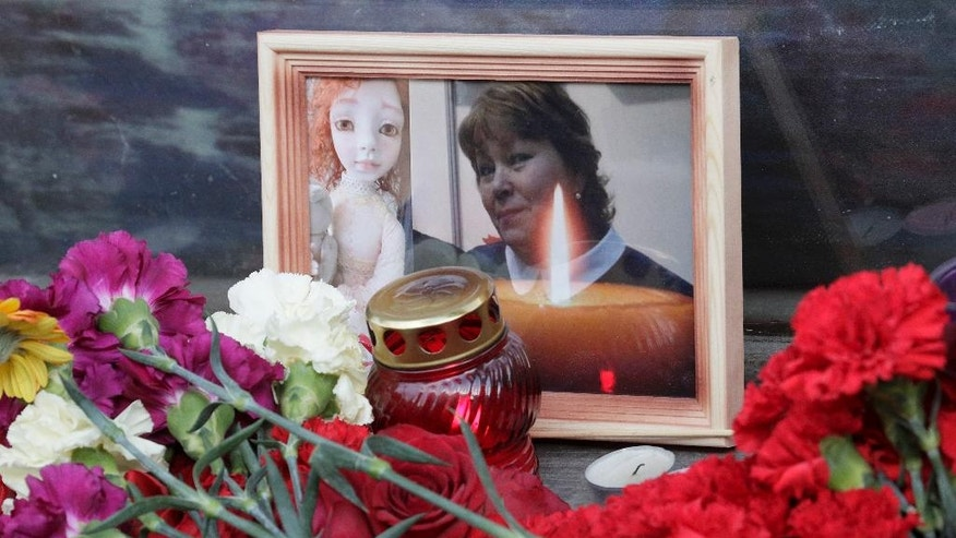 CLARIFIES THE EVENTS ABOUT THE DEATH OF THE CHILD A photograph of Irina Medyantseva, one of the victims of the subway explosion, is placed at a makeshift memorial at the Tekhnologichesky Institute subway station in St. Petersburg, Russia, Wednesday April 5, 2017.  Relatives said that the creative doll maker Medyantseva, died after she threw herself onto her daughter to save her from the bomb blast in the subway in Russia's St. Petersburg on Monday April 3. (AP Photo/Dmitri Lovetsky)