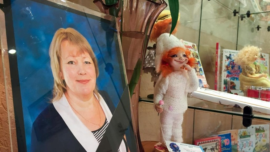 CLARIFIES THE EVENTS ABOUT THE DEATH OF THE CHILD  A picture of doll-maker Irina Medyantseva, one of the victims of the subway bombing, stands at a makeshift memorial next to one of her dolls at a community center in St. Petersburg, Russia, Wednesday, April 5, 2017. Relatives said that the creative doll maker Medyantseva, died after she threw herself onto her daughter to save her from the bomb blast in the subway in Russia's St. Petersburg Monday April 3.(AP Photo/Iuliia Subbotovska)