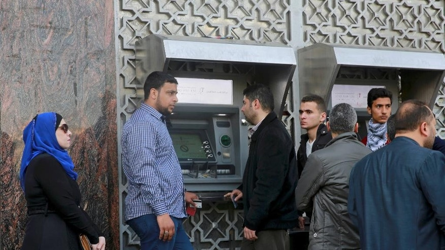 Employees wait in line in front of a cash machine to receive their monthly salaries in Gaza City, Wednesday, April 5, 2017. The cash-strapped Palestinian Authority said it has slashed the salaries of some 50,000 government employees in the Gaza Strip who have been sitting idly since the rival Hamas militant group took over the territory a decade ago. Spokesman Yousif al-Mahmoud says that salaries would be cut by 30 percent because of a reduction in foreign aid. (AP Photo/Adel Hana)