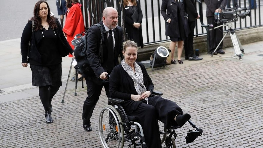 "Injured U.S. tourist Melissa Cochran, whose husband Kurt Cohran was killed in the March 22 London terror attack, arrives for a ""Service of Hope"" at Westminster Abbey, two weeks after the attack, in London, Wednesday, April 5, 2017. The service took place near Westminster Bridge, where Khalid Masood mowed down pedestrians before stabbing a police officer outside Parliament. (AP Photo/Matt Dunham)"