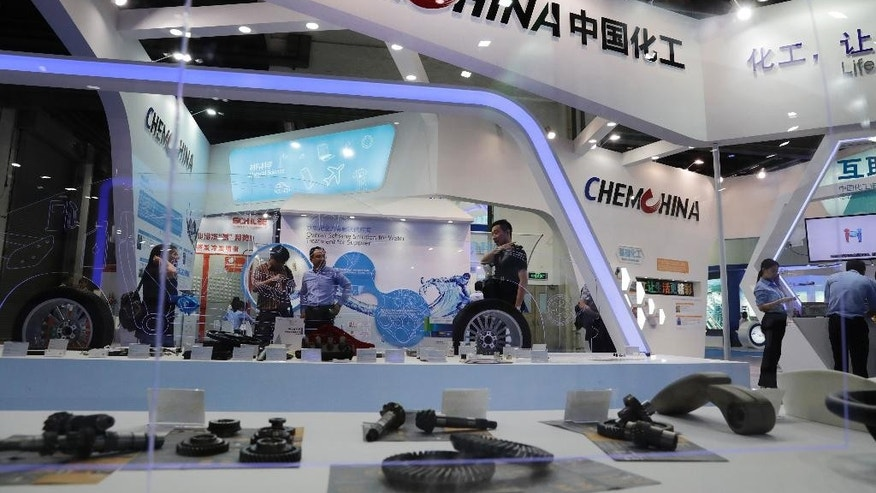 CORRECTS DATE -  FILE - In this Sept. 21, 2016 file photo, visitors tour the exhibition booth of ChemChina, also known as China National Chemical Corp., during the China International Chemical Industry Fair in Shanghai, China. U.S. regulators have agreed to the Chinese conglomerate's proposed $43 billion acquisition of Swiss agribusiness giant Syngenta on condition it sells some businesses to satisfy anti-monopoly objections. The Federal Trade Commission's announcement on Tuesday, April 4, 2017, follows approval last year by European regulators of the purchase by state-owned ChemChina. It would be China's biggest foreign acquisition to date. (AP Photo/Andy Wong, File)