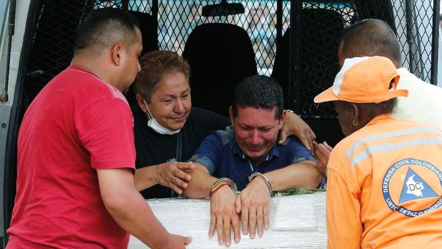 Prison inmate Ricardo Alegria, center, cries over of the coffin containing his daughter's remains, in Mocoa, Colombia, Monday, April 3, 2017. Alegria was allowed out of prison to attend her funeral, after she died in a deadly avalanche of floodwaters, mud and debris caused by heavy rains, that killed more than 260 people and leaving many more injured and homeless. (AP Photo/Fernando Vergara)