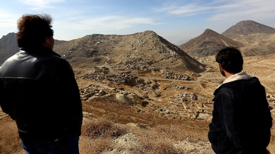 FILE - In this Sunday, Jan. 18, 2015, file photo, Abdul Qadir Timor, director of archaeology at the Ministry of Information and Culture, left, looks at the view of Mes Aynak valley, some 40 kilometers (25 miles) southwest of Kabul, Afghanistan. The Afghan government is trying to grab President Donald Trump's attention by dangling its massive, untouched wealth of minerals, including lithium, the silvery metal used in mobile phone and computer batteries considered essential to modern life. But tapping into that wealth, which also includes coal, copper, rare earths and far more, is likely a long way off, with security worsening the past year and Trump's policy on the war still not known. (AP Photo/Rahmat Gul, file)