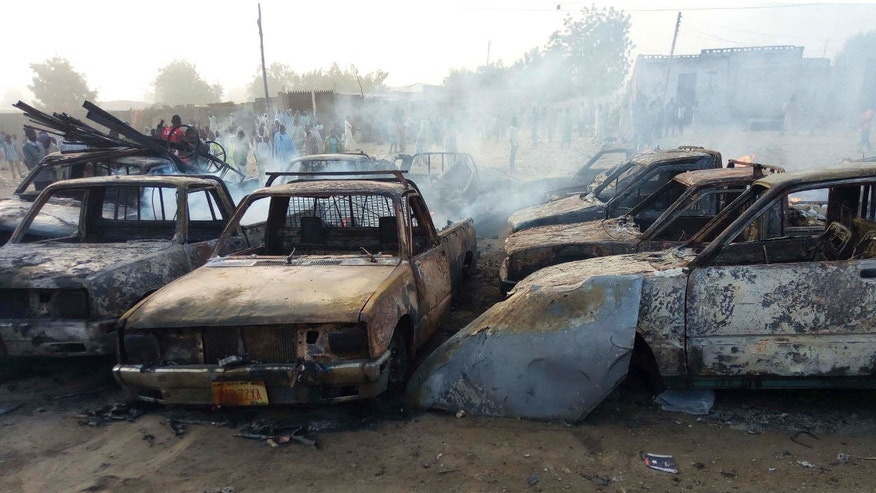 FILE- In this Friday, Feb. 17, 2017 file photo, people stand behind burnt out cars following a suicide bomb attacked in Maiduguri, Nigeria.