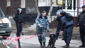 Russian police officer with a sniffing dog crosses a police line in St.Petersburg, Russia Thursday, April 6, 2017. Russian investigators on Thursday found elements of an explosive device in the apartment where they lived. The building's residents had been evacuated before explosives experts went in to check the site. (Yevgeny Stepanov/Interpress photo via AP)