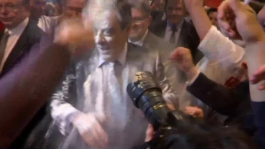"Conservative French presidential candidate Francois Fillon is doused with flour while arriving at a political meeting in the eastern city of Strasbourg, Thursday April 6, 2017.  A young man wearing a T-shirt marked ""Students with Fillon"" was seen on BFM TV throwing flour at the candidate Thursday night as Fillon walked among supporters, completely covering Fillon's face, shoulders and chest with white powder.(BFMTV via AP) MANDATORY CREDIT"