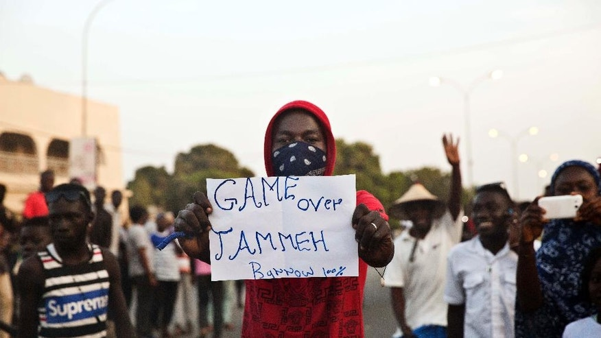 FILE - In this Thursday, Jan. 19, 2017 file photo, A man holds a banner as Gambians cheers in Serrekunda, Gambia.  Many Gambians hope to secure a transition from decades of dictatorship to democracy on Thursday, April 6, 2017, as they vote in parliamentary elections, the first since longtime leader Yahya Jammeh flew into exile in January. (AP Photo/Jerome Delay, File)