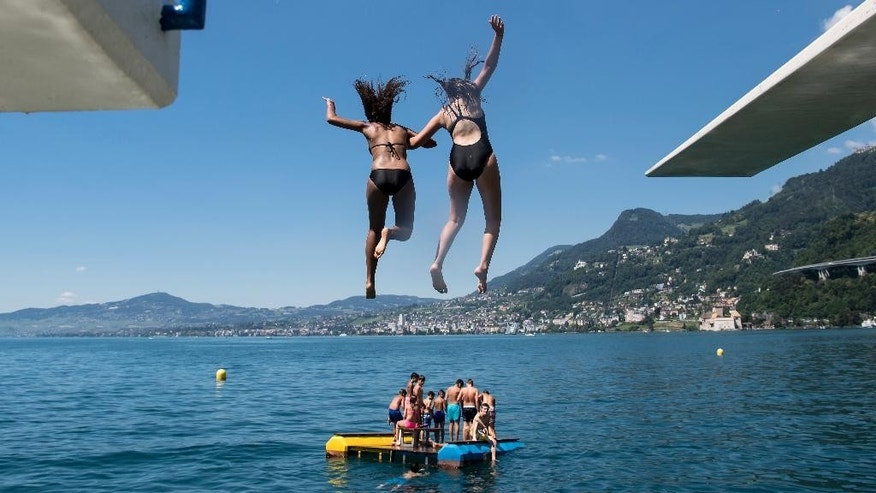 FILE - In this July 9, 2016 file photo, girls jump from a diving platform into the Geneva Lake and enjoy sunny and warm weather, in Villeneuve, Switzerland. After nearly 90 years, women can legally swim topless in Geneva's lake and Rhone River without running the risk of a fine. Geneva's regional council has voted to modify a 1929 ordinance that banned women from swimming topless in the city's main natural waterways, though the change doesn't apply to public swimming pools or swimming totally naked. Nicolas Bolle, an official with Geneva's security department, on Thursday, April 6, 2017 confirmed the council's action a day earlier. (Jean-Christophe Bott/Keystone via AP,file)