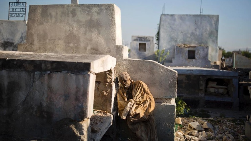 In this March 29, 2017 photo, the remains of an exhumed corpse leans against its grave before being taking away to a mass grave in the national cemetery in Port-au-Prince, Haiti. Many bereaved Haitians go into a lifetime of debt to send off deceased relatives. Burial costs average $5,000 per household - well over than what most Haitians earn in a year. (AP Photo/Dieu Nalio Chery)