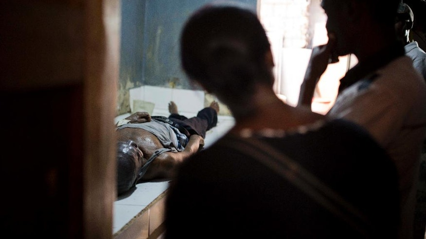 In this March 29, 2017 photo, Aspasia Tanis, left stands next to her brother while looking at the body of their dead father at the Zenith Funeral Home and Morgue in Port-au-Prince, Haiti. The distraught single mother is frantically seeking loans from friends and pastors to pay for the cheapest funeral on offer. (AP Photo/Dieu Nalio Chery)