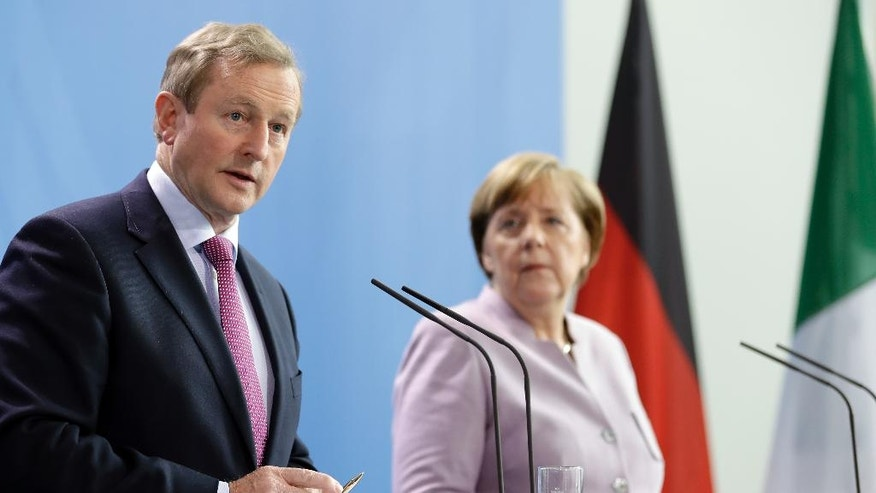 German Chancellor Angela Merkel, right, and Irish Prime Minister Enda Kenny, left, address the media during a joint statement prior to a meeting at the Chancellery in Berlin, Germany, Thursday, April 6, 2017. (AP Photo/Michael Sohn)