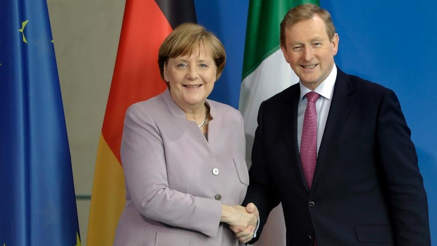 German Chancellor Angela Merkel, right, and Irish Prime Minister Enda Kenny, left, shake hands after a joint statement prior to a meeting at the Chancellery in Berlin, Germany, Thursday, April 6, 2017. (AP Photo/Michael Sohn)