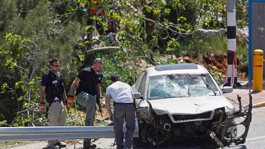 Israeli security forces and emergency personnel inspect the scene of a Palestinian car ramming attack not far from the Israeli settlement of Ofra near the West Bank city of Ramallah, Thursday, April 6, 2017. A Palestinian was apprehended after he rammed his vehicle into a group of people in the West Bank on Thursday morning, killing one Israeli and injuring another, the Israeli military said. (AP Photo/Majdi Mohammed)
