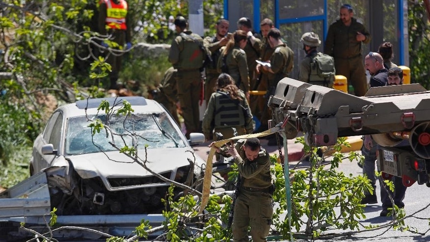 Israeli security forces and emergency personnel prepare to remove a vehicle after a car ramming attack not far from the Israeli settlement of Ofra near the West Bank city of Ramallah, Thursday, April 6, 2017. A Palestinian was apprehended after he rammed his vehicle into a group of people in the West Bank on Thursday morning, killing one Israeli and injuring another, the Israeli military said. (AP Photo/Majdi Mohammed)
