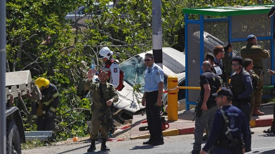 Israeli security forces and emergency personnel inspect the scene of a car ramming attack not far from the Israeli settlement of Ofra near the West Bank city of Ramallah, Thursday, April 6, 2017. A Palestinian was apprehended after he rammed his vehicle into a group of people in the West Bank on Thursday morning, killing one Israeli and injuring another, the Israeli military said. (AP Photo/Majdi Mohammed)