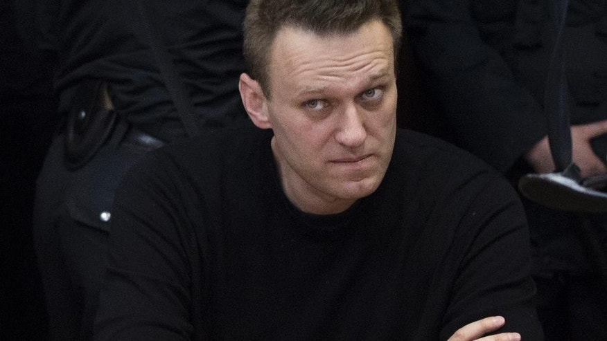 FILE- In this file photo taken on Thursday, March 30, 2017, Russian opposition leader Alexei Navalny sits in court in Moscow, Russia.  Navalny, who organized nationwide anti-corruption protests last month and was arrested immediately on arrival at the rally in Moscow, told The Associated Press that he will continue to campaign to cancel a ban which barres him running for president, before he prepares to run against President Vladimir Putin in the 2018 election. (AP Photo/Pavel Golovkin, file)