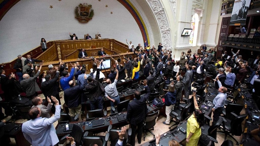 Opposition lawmaker raise their hands to approve activation of the procedure to remove magistrates from the Supreme Court during a session at the National Assembly in Caracas, Venezuela, Wednesday, April 05, 2017. The government over the weekend backed away from the Supreme Court's ruling after strong international and domestic criticism. (AP Photo/Ariana Cubillos)