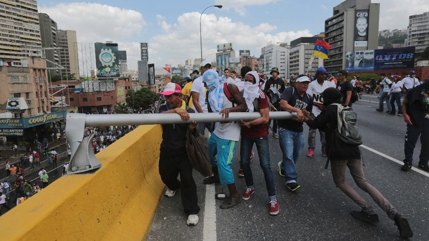 Demonstrators remove a fence to make a barricade during a protest in Caracas, Venezuela, Thursday, April 6, 2017. Tens of thousands of demonstrators shut down Venezuela's capital on Thursday, blocking the city's main artery to protest what they call an attempted coup by the socialist administration. (AP Photo/Fernando Llano)