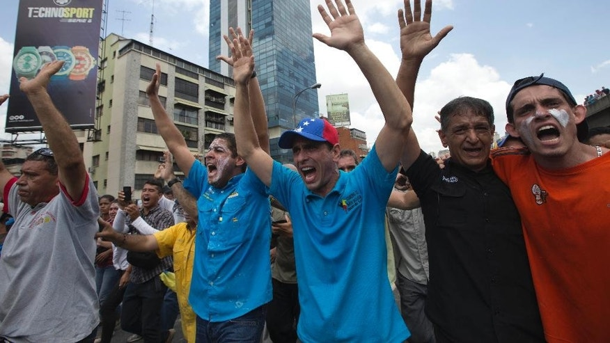 Governor of Miranda State and opposition leader Henrique Capriles, wearing a hat, raises his hands along with other demonstrators calling for the Bolivarian National Guard to stop firing tear gas during a protest in Caracas, Venezuela, Thursday, April 6, 2017. The South American country has seen near-daily protests since the Supreme Court issued a ruling nullifying congress last week. The court pulled that decision back after it came under heavy criticism, but opposition leaders said the attempt to invalidate a branch of power revealed the administration's true dictatorial nature. (AP Photo/Ariana Cubillos)