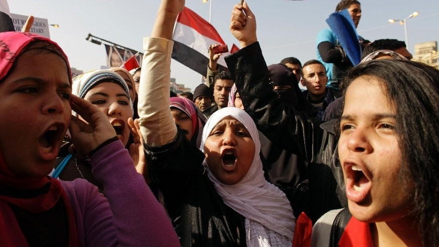 FILE - In this Jan. 25, 2012 file photo, Egyptian girls chant slogans in Tahrir Square during a rally to mark the one year anniversary of the uprising that ousted President Hosni Mubarak in Cairo, Egypt. Hundreds of Egyptian women and girls have come out to denounce sexual harassment and share personal stories about it on social media, breaking a taboo and raising the ire of the country's conservative majority. In posts on Facebook and Twitter from the weekend to Wednesday, rare, candid stories focused on women's first experiences of harassment, almost all of which occurred in childhood and some involving family members and teachers. (AP Photo/Maya Alleruzzo, File)