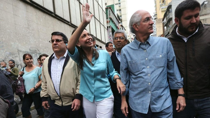 FILE - In this Dec. 3, 2014 file photo, former Congresswoman and opposition leader Maria Corina Machado arrives to the Attorney General Office to testify, accompanied by Caracas Mayor Antonio Ledezma, in Caracas, Venezuela. The most-voted-for lawmaker in Venezuela's 2010 congressional elections, Machado was stripped of office in 2014. Ledezma was arrested in February 2015 for allegedly being part of a U.S.-backed plot to topple Maduro. Three months later, he was placed under house arrest while awaiting trial. (AP Photo/Ariana Cubillos, File)