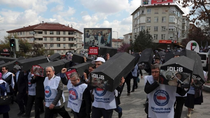 Dozens of members of a Turkish trade union carry black-painted coffins with images of the attack's child victims in protest of this week's chemical weapons attack that killed more than 80 people in northern Syria, in Ankara, Turkey, Friday, April 7, 2017. The group of some 250 members of a pro-government union on Friday held funeral prayers for the victims of the assault in front of the Iranian embassy in Ankara, before marching to the Russian embassy.(AP Photo/Burhan Ozbilici)