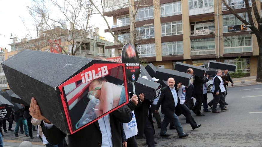 Dozens of members of a Turkish trade union carry black-painted coffins with images of the attack's child victims, in protest of this week's chemical weapons attack that killed more than 80 people in northern Syria, in Ankara, Turkey, Friday, April 7, 2017. The group of some 250 members of a pro-government union on Friday held funeral prayers for the victims of the assault in front of the Iranian embassy in Ankara, before marching to the Russian embassy.(AP Photo/Burhan Ozbilici)