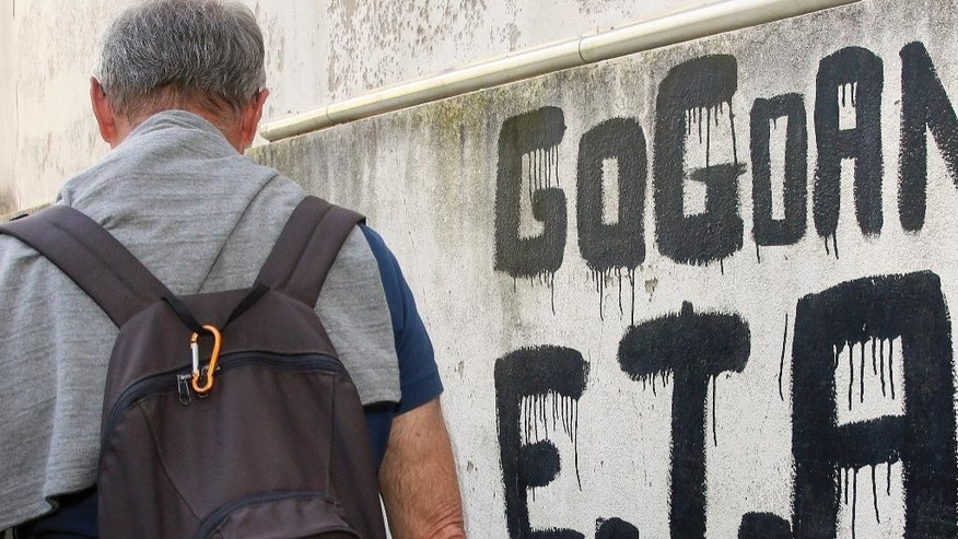 "A man walks past graffiti reading ""ETA , Basque country and Freedom"", in Sare, southwestern France, Friday, April 7, 2017. The armed Basque separatist group ETA, inactive for more than five years, is to hand over its arms Saturday, a finishing touch to a 43-year violent campaign that claimed 829 lives, mostly in Spain. (AP Photo/Bob Edme)"