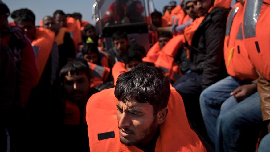 Migrants are rescued from a rubber boat by members of Proactiva Open Arms NGO, in the Mediterranean sea, about 56 miles north of Sabratha, Libya, Thursday, April 6, 2017.  Many fences are still being erected across much of Serbia and Croatia to stop the flow of migrants along the land route into central Europe, but these migrants will be taken direct to Trapani, Italy.  (AP Photo/Bernat Armangue)