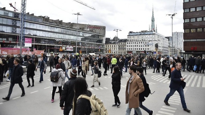 People walk away fro  the scene after a truck crashed into a department store injuring several people in central Stockholm, Sweden, Friday April 7, 2017. (Noella Johansson TT News Agency via AP)