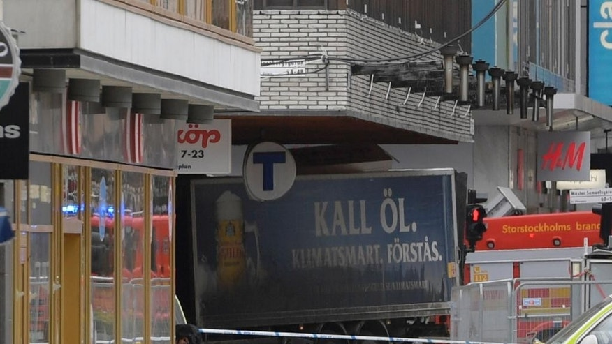 The rear of a truck, left, protrudes after it crashed into a department store injuring several people in central Stockholm, Sweden, Friday April 7, 2017. (Anders Wiklund , TT News Agency via AP)