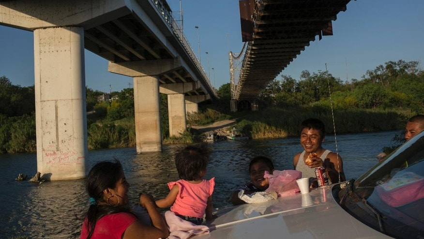 In this Wednesday, March, 22, 2017 photo, a family picnics on the banks of the Rio Grande in Miguel Aleman, Tamaulipas state, Mexico, located across the river from Roma, Texas. (AP Photo/Rodrigo Abd)