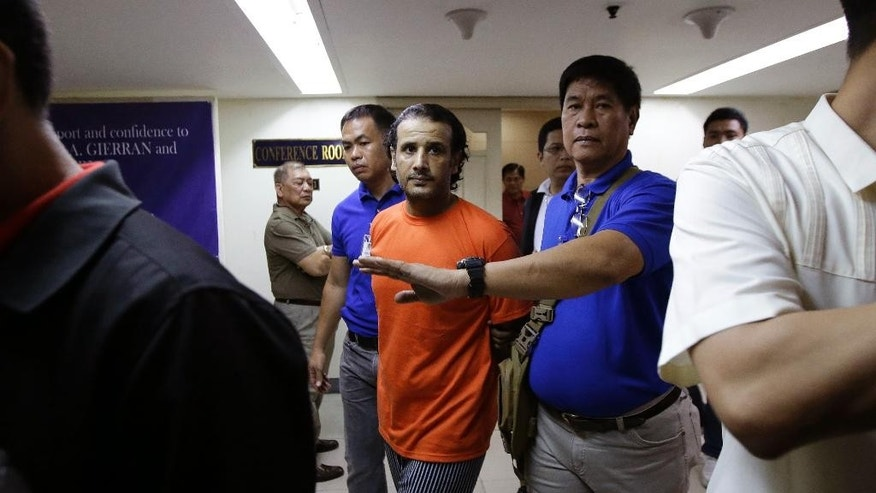 In this Thursday, April 6, 2017 photo, a suspected member of the Islamic State group, Hussein Aldhafiri, center in orange shirt, is escorted by security men at the National Bureau of Investigation in Manila, Philippines. Philippine officials aid Friday U.S. and Kuwaiti security officials helped them identify and arrest a Middle Eastern couple with suspected links to the Islamic State group and who may have the capability to launch bomb attacks. (AP Photo/Aaron Favila)
