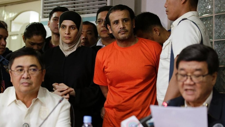 In this Thursday, April 6, 2017 photo, suspected members of the Islamic State group, Hussein Aldhafiri, top center in orange shirt, and Rahaf Zina Dhafiri, top left, are presented to reporters by Justice Secretary Vitaliano Aguirre II, bottom right, during a press conference at the National Bureau of Investigation in Manila, Philippines. Philippine officials aid Friday U.S. and Kuwaiti security officials helped them identify and arrest a Middle Eastern couple with suspected links to the Islamic State group and who may have the capability to launch bomb attacks. (AP Photo/Aaron Favila)