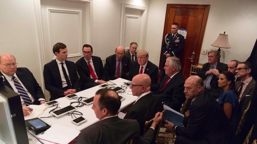 In this image provided by the White House, President Donald Trump receives a briefing on the Syria military strike from his National Security team after the strike at Mar-a-Lago in Palm Beach, Fla., Thursday night, April 6, 2017. (White House via AP)
