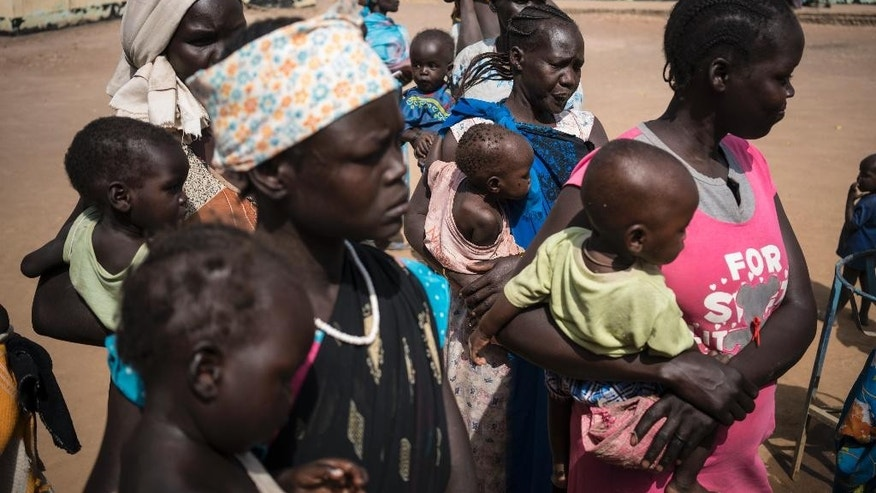 In this photo taken Monday, March 13, 2017, mothers hold their children as they wait to have them screened for malnutrition at a UNICEF-supported Outpatient Therapeutic Program in Aweil, South Sudan. The United Nations said Saturday, April 8, 2017 that civilians and aid workers in South Sudan have seen an alarming rise in attacks and harassment in the past week as the country faces both civil war and famine, accusing both government and opposition forces. (Mackenzie Knowles-Coursin/UNICEF via AP)