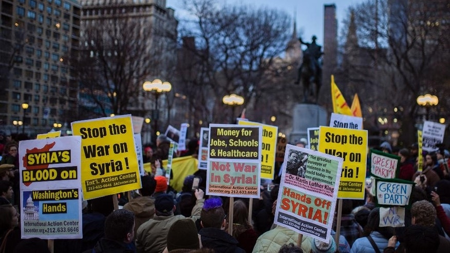 Protesters carry placards during a rally against the U.S. missile strikes in Syria, Friday, April 7, 2017, in New York. The U.S. fired a barrage of cruise missiles into Syria on Thursday night in retaliation for a chemical weapons attack against civilians earlier in the week. (AP Photo/Andres Kudacki)