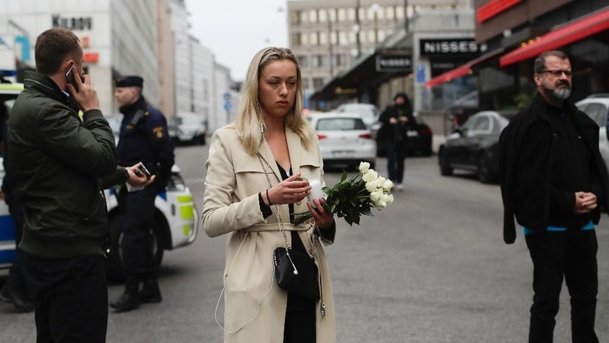 "A woman prepares to offer flowers near the department store Ahlens following a suspected terror attack in central Stockholm, Sweden, Saturday, April 8, 2017. A Swedish prosecutor says a person has been formally identified as a suspect ""of terrorist offenses by murder"" by driving a hijacked truck into a crowd of pedestrians. (AP Photo/Markus Schreiber)"