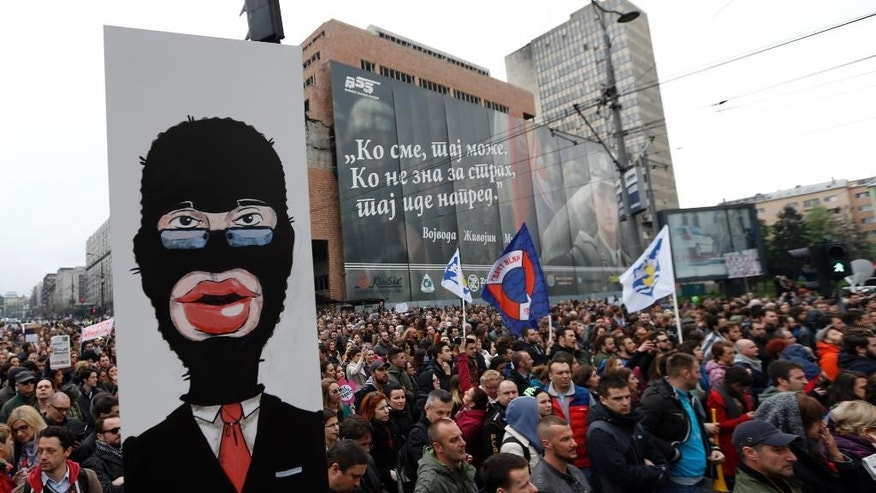 A protester holds a banner depicting Serbian Prime Minister Aleksandar Vucic, during a protest in Belgrade, Serbia, Saturday, April 8, 2017. Some thousands of people are blowing whistles and banging pots outside the Serbian government headquarters to protest the election of powerful Prime Minister Aleksandar Vucic as the country's new president. (AP Photo/Darko Vojinovic)
