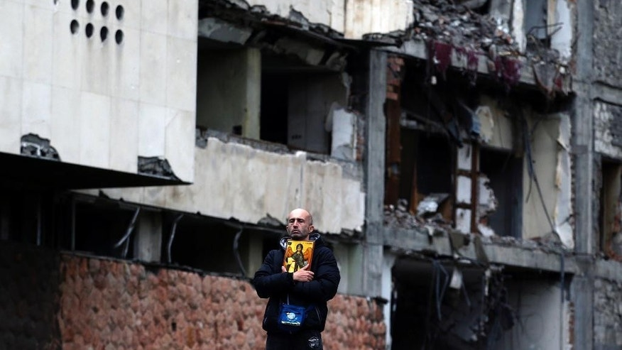 A man holds an icon and stands in front of the destroyed former Yugoslav army headquarters, during a protest in Belgrade, Serbia, Saturday, April 8, 2017. Thousands of people are blowing whistles and banging pots outside the Serbian government headquarters to protest the election of powerful Prime Minister Aleksandar Vucic as the country's new president. (AP Photo/Darko Vojinovic)