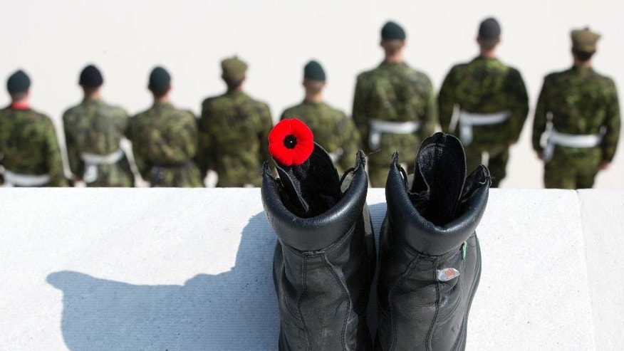Canadian soldiers stand in a line in front of a black boot with a red poppy, representing the fallen, at the WWI Canadian National Vimy Memorial in Givenchy-en-Gohelle, France on Friday, April 7, 2017. Commemoration ceremonies will take place on Sunday at the memorial to honor Canadian soldiers who were killed or wounded during the Battle of Vimy Ridge in April 1917. (AP Photo/Virginia Mayo)