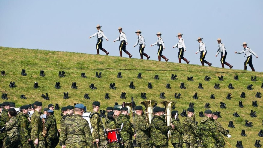 Canadian soldiers and Canadian Mounted Police practice marching in front of black boots, representing the fallen, at the WWI Canadian National Vimy Memorial in Givenchy-en-Gohelle, France on Friday, April 7, 2017. Commemoration ceremonies will take place on Sunday at the memorial to honor Canadian soldiers who were killed or wounded during the Battle of Vimy Ridge in April 1917. (AP Photo/Virginia Mayo)