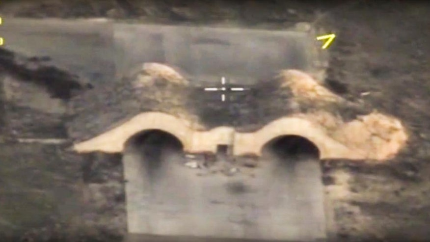 FILE - In this file photo made from the footage taken from Russian Defense Ministry official web site Friday, April 7, 2017, an aerial view shows shelters for aircraft at a Syrian airbase after it was hit by US strike in Syria. A U.S. missile attack on Friday, April 7, 2017 has caused heavy damage to one of Syria's biggest and most strategic air bases, used to launch warplanes to strike opposition-held areas in central, northern and southern Syria. (Russian Defense Ministry Press Service Photo via AP, File)