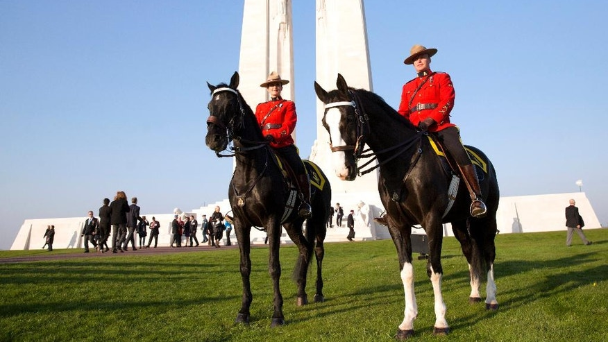 Two Canadian Mounted Police sit on their horses prior to a sunset ceremony and mounting of the vigil at the WWI Canadian National Vimy Memorial in Givenchy-en-Gohelle, France on Saturday, April 8, 2017. Commemoration ceremonies will take place on Sunday at the memorial to honor Canadian soldiers who were killed or wounded during the Battle of Vimy Ridge in April 1917. (AP Photo/Virginia Mayo)