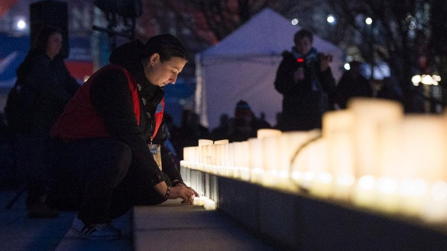 A woman turns on electronic candles during a vigil to commemorate the 100th anniversary of the Battle of Vimy Ridge in Ottawa, Ontario, on Saturday, April 8, 2017. (Justin Tang/The Canadian Press via AP)