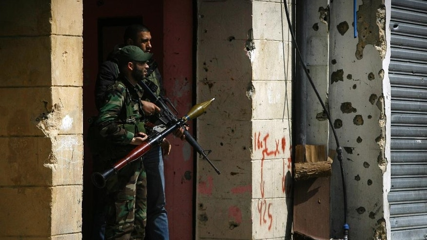 A member of the Palestinian Fateh Movement prepares to fires an RPG during a clashes that erupted between the Palestinian Fatah Movement and Islamists in the Palestinian refugee camp of Ein el-Hilweh near the southern port city of Sidon, Lebanon, Sunday, April 9, 2017. Ein el-Hilweh, the largest of 12 Palestinian refugee camps in Lebanon, is notorious for its lawlessness and is home to some extremists who sympathize with the Islamic State group and al-Qaida. (AP Photo/Mohammed Zaatari)