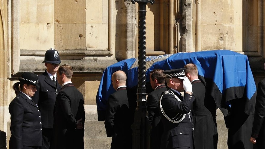A coffin carrying the late PC Keith Palmer, who was killed in the London attack on March 22, is carried into the Houses of Parliament to rest overnight in the Chapel of St Mary Undercroft in London, Sunday, April 9, 2017. Palmer's funeral is due to take place at Southwark Cathedral in London on Monday. (AP Photo/Matt Dunham)