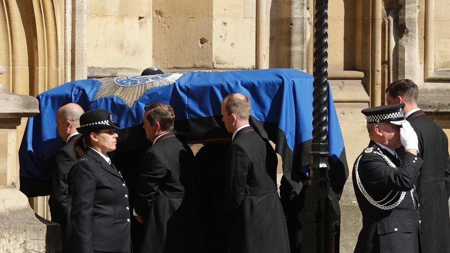 Pallbearers carrying the coffin of late police constable Keith Palmer, who was killed in the London attack on March 22, is carried into the Houses of Parliament to rest overnight in the Chapel of St Mary Undercroft,  in London, Sunday, April 9, 2017. Palmer's funeral is due to take place at Southwark Cathedral in London on Monday. (AP Photo/Matt Dunham)