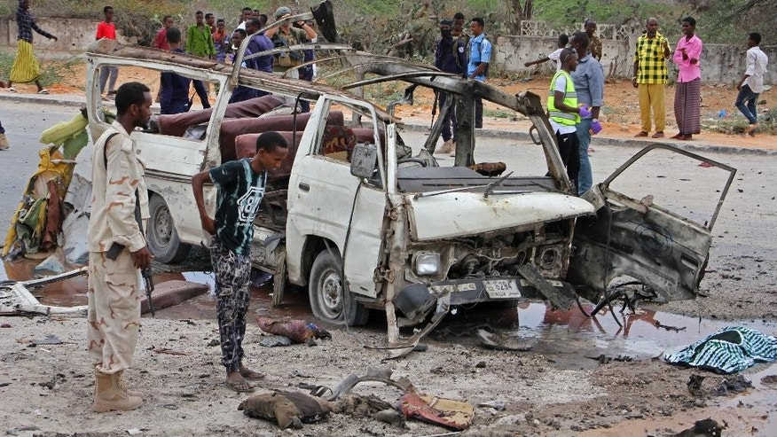 A Somali soldier, left, stands by the wreckage of a passing minibus that was destroyed in a suicide car bomb attack near the defense ministry compound in Mogadishu, Somalia Sunday, April 9, 2017. Somalia's new military chief Gen. Mohamed Ahmed Jimale survived the blast which targeted the convoy he was traveling in with senior military officials, police say, but a number of soldiers and civilians were killed. (AP Photo/Farah Abdi Warsameh)